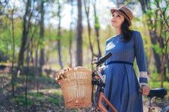 Ung dam i en hatt, i en parkera med hennes tappningcykel Arkivbild