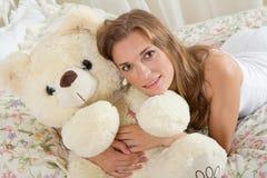 Ung dam i säng med nallebjörnen arkivfoton