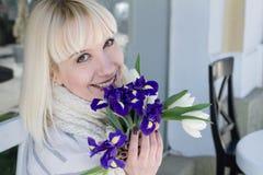 Ung dam med en bukett av violetta iriers och den vita tulpanenjoen arkivbilder