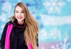 Ung dam med långt blont hår och perfekt makeup som ser kameran och ler, utomhus- skytte i staden Royaltyfri Fotografi