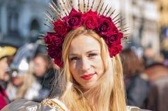 Ung dam med röda rosor under den Venetian karnevalet arkivfoton