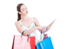 Ung dam på shopping som kontrollerar eller packar ihop på minnestavlan Royaltyfri Foto