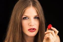 Ung dam som äter en jordgubbe Arkivbild