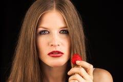 Ung dam som äter en jordgubbe Arkivfoto