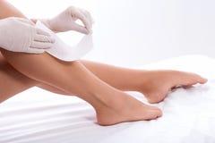Ung dam som applicerar vaxremsan på benet Fotografering för Bildbyråer