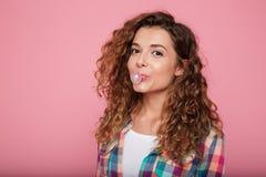 Ung dam som blåser bubbelgum som isoleras över rosa färger Arkivbilder
