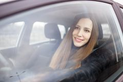 Ung dam som kör en bil i vinter fotografering för bildbyråer
