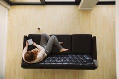 Ung dam som kopplar av på en soffa genom att använda den digitala minnestavlan royaltyfria bilder