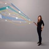 ung dam som rymmer en telefon med färgrika linjer Arkivbilder