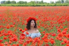 Ung dam som sitiing i vallmo Fotografering för Bildbyråer