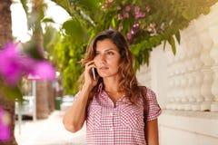 Ung dam som talar på mobiltelefonen och bort ser Fotografering för Bildbyråer