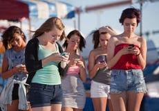 Ung damtoalett som använder deras telefoner Royaltyfri Foto