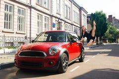 Ung dansare som hoppar nära den röda bilen royaltyfri fotografi