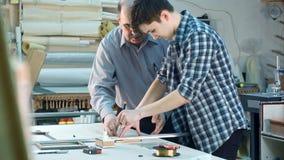 Ung deltagare i utbildning som försöker att klippa ett exponeringsglas för ramen, hålla ögonen på för seniourarbetare Royaltyfri Bild