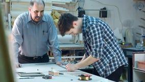 Ung deltagare i utbildning som konstruerar en ram bak skrivbordet i ramseminarium Royaltyfria Foton