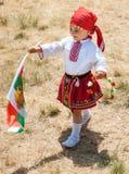 Ung deltagarefestival Rozhen i nationell dräkt och den bulgariska flaggan arkivbilder