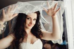 Ung den brunettskönhet eller bruden, bak en vit skyler Arkivbilder