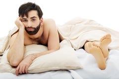 Ung deprimerad man i säng Royaltyfri Fotografi