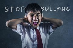 Ung desperat missbrukad skolpojke som skriker gråta offret av att trakassera och missbruk på skola på svart tavla i den hunsade u fotografering för bildbyråer