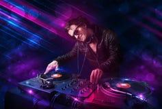 Ung discjockey som spelar på skivtallrikar med ljusa effekter för färg Royaltyfri Bild