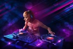 Ung discjockey som spelar på skivtallrikar med ljusa effekter för färg Arkivfoto