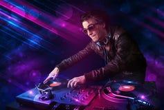 Ung discjockey som spelar på skivtallrikar med ljusa effekter för färg stock illustrationer