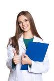 Ung doktor för kvinnlig student med en minnestavla på en vit bakgrundsvisningtumme Royaltyfria Bilder