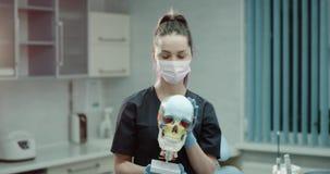Ung doktorsassistent som bär en kirurgisk maskering och handskar och framme av kameran i ett modernt klinikrum som undersöker a lager videofilmer