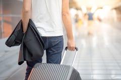 Ung dräkt och bagage för Asain maninnehav i flygplatsterminal Arkivfoton