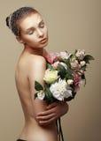 Ung drömlik kvinna med buketten av blommor arkivbilder