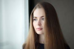 Ung drömlik kvinna nära fönster hemma, closeup upp ståenden för naturligt ljus royaltyfria foton
