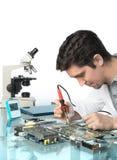 Ung driftig manlig tech eller teknikern reparerar elektronisk equipme Arkivbild