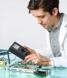 Ung driftig manlig tech eller teknikern reparerar elektronisk equipme Royaltyfri Bild