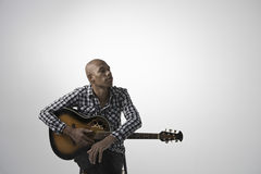 Ung eftertänksam man med gitarren Arkivfoto
