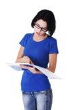 Ung eftertänksam student som läser henne anmärkningar Fotografering för Bildbyråer