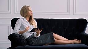 Ung elegant affärskvinna som använder den digitala minnestavlan, medan ligga på soffan lager videofilmer