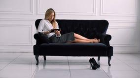 Ung elegant affärskvinna som använder den digitala minnestavlan, medan ligga på soffan arkivfilmer