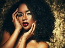 Ung elegant afrikansk amerikankvinna med afro hår Spika manicured polermedel spikar guld- bakgrund Arkivfoto