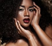Ung elegant afrikansk amerikankvinna med afro hår Spika manicured polermedel spikar guld- bakgrund royaltyfri foto