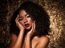 Ung elegant afrikansk amerikankvinna med afro hår Spika manicured polermedel spikar guld- bakgrund Royaltyfria Bilder