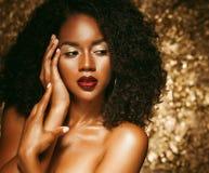 Ung elegant afrikansk amerikankvinna med afro hår Spika manicured polermedel spikar guld- bakgrund arkivbild