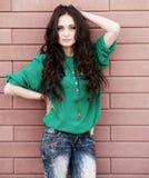 Ung elegant kvinna på en backround för tegelstenvägg Fotografering för Bildbyråer