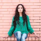 Ung elegant kvinna på en backround för tegelstenvägg Royaltyfri Fotografi