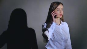 Ung elegant kvinna som talar på mobiltelefonen mot svart bakgrund med skugga arkivfilmer