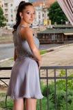 Ung elegant lycklig flicka i den gråa klänningen som framme poserar av staketet i restaurangträdgård royaltyfria foton