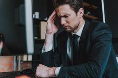 Ung elegant man som har huvudvärk och stänger hans ögon arkivfoto