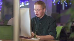 Ung emotionell man i exponeringsglas som framme sitter på hans arbetsplats av den moderna datoren i stort kontor Arbetaren uttryc lager videofilmer