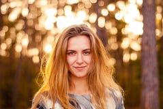 Ung ensam flicka som ler på solnedgången i skogen Royaltyfria Foton
