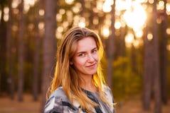 Ung ensam flicka som ler på solnedgången i skogen Arkivbild
