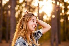 Ung ensam flicka som ler på solnedgången i skogen Royaltyfri Foto